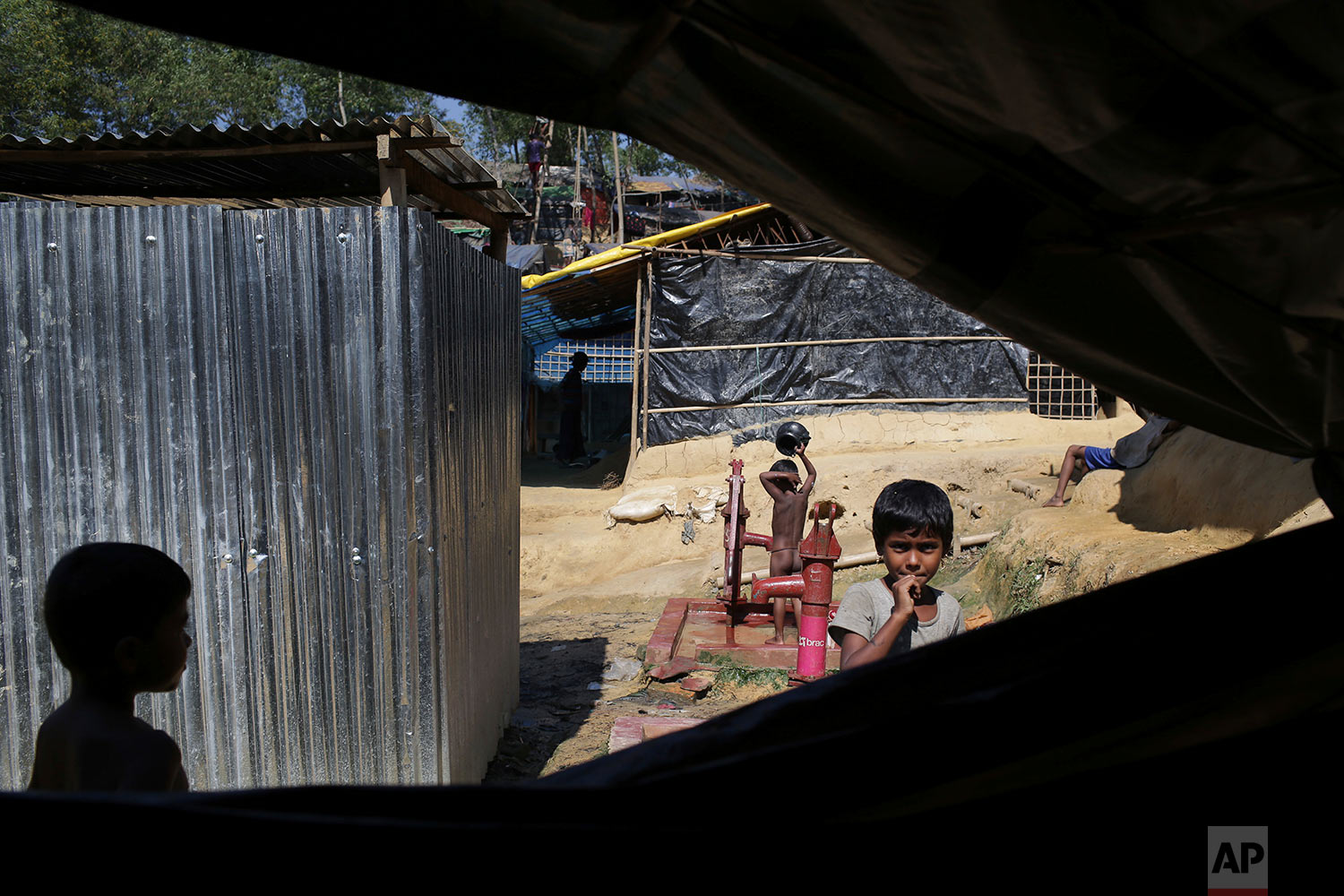 "Rohingya Muslim children walk around their tents while one child bathes in Kutupalong Refugee camp on Monday, Nov. 20, 2017, in Bangladesh. More than 620,000 Rohingya have fled Rakhine for neighboring Bangladesh since late August, when the military launched what it called ""clearance operations"" in response to insurgent attacks. (AP Photo/Wong Maye-E)"
