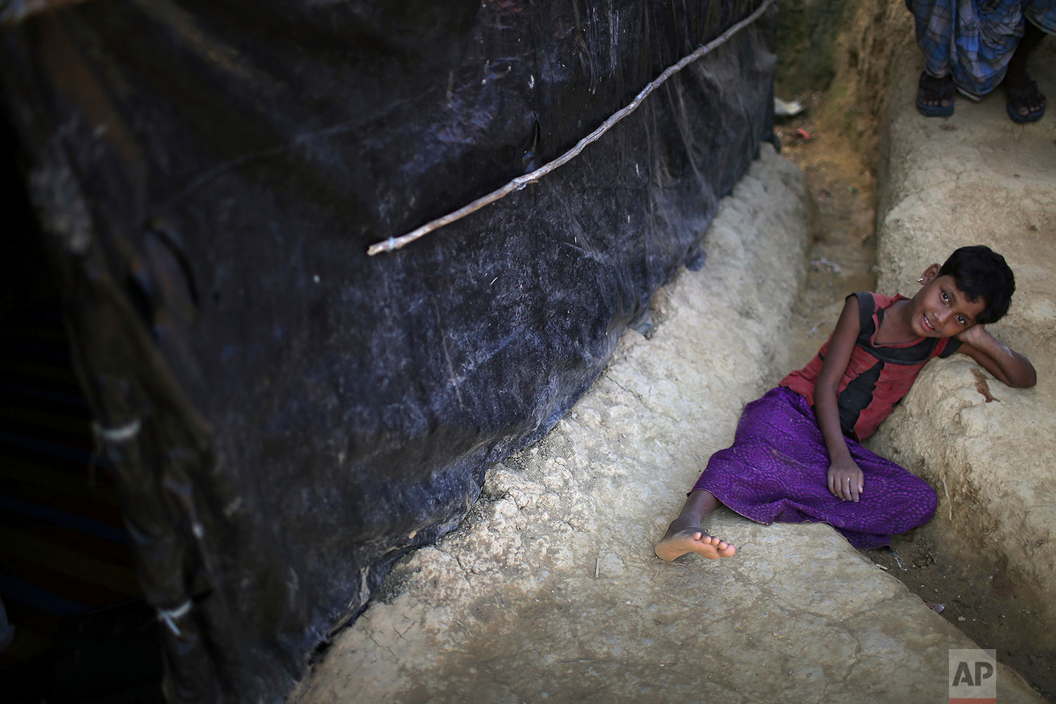 "In this Sunday, Nov. 19, 2017, photo, a Rohingya Muslim girl rests in the drain of a mud track in Kutupalong refugee camp in Bangladesh.  More than 620,000 Rohingya have fled Rakhine for neighbouring Bangladesh since late August 2017, when the military launched what it called ""clearance operations"" in response to insurgent attacks. (AP Photo/Wong Maye-E)"