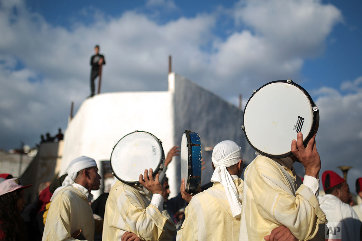 In this Thursday Nov. 30, 2017 photo, a traditional band shelter themselves from the sun as they take part in an annual parade celebrating the birth anniversary of Prophet Muhammad, in Sale, near Rabat, Morocco. (AP Photo/Mosa'ab Elshamy)