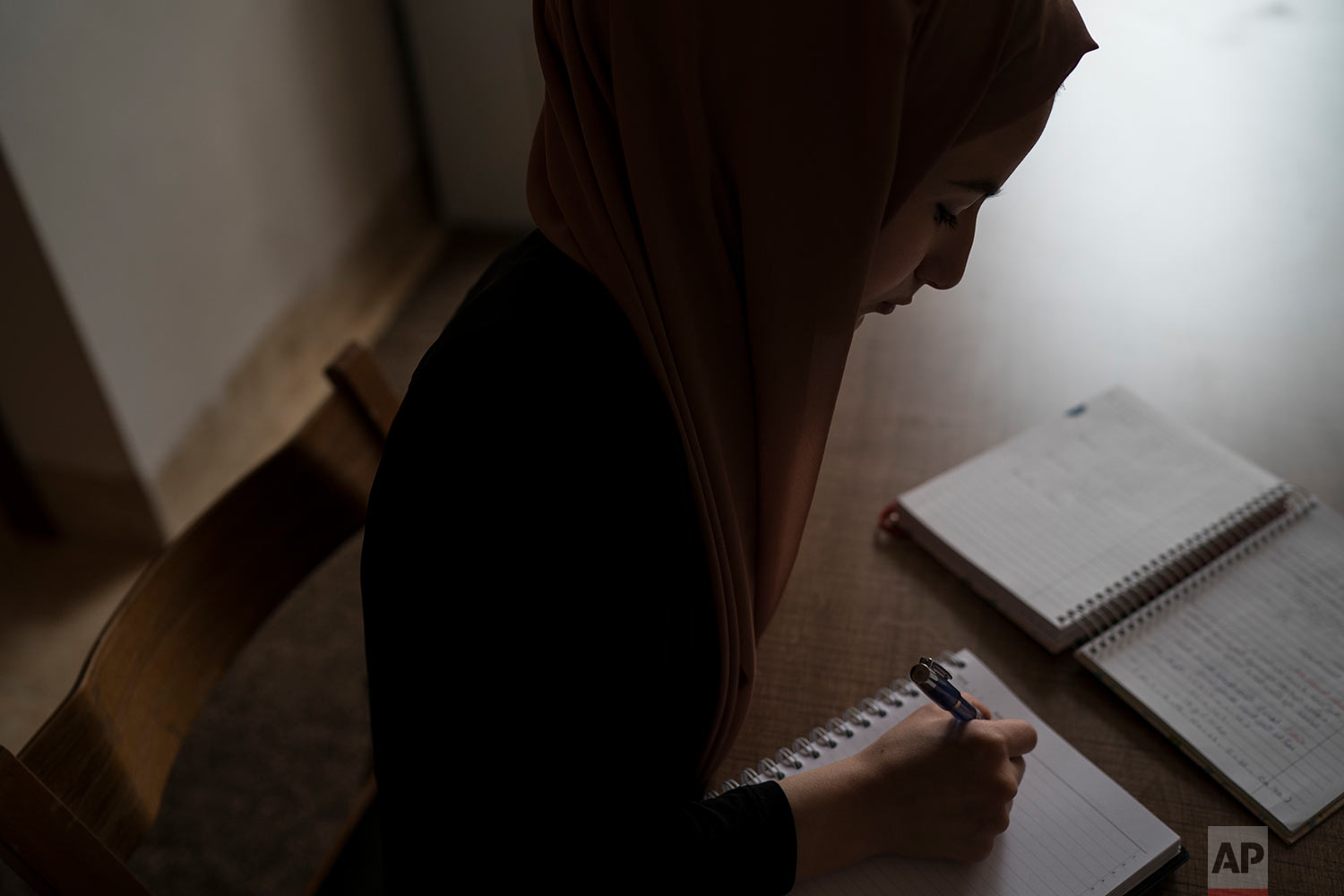Ferah says writing helped her endure during the rule of the Islamic State group over her home city of Mosul, giving her an outlet to explore her fears and hopes. (AP Photo/Felipe Dana)