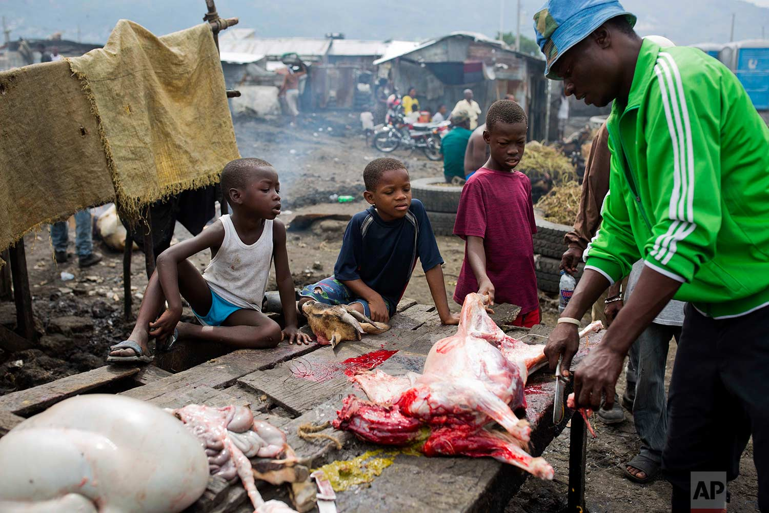 In this Nov. 10, 2017 photo, children watch a butcher portion a goat carcass at the La Saline slaughterhouse, in Port-au-Prince, Haiti. (AP Photo/Dieu Nalio Chery)