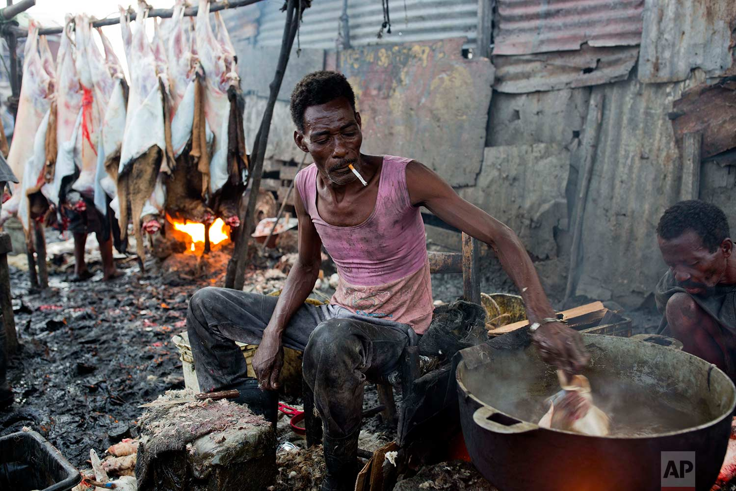 "In this Nov. 9, 2017 photo, Gesner Sagaille stirs a goat's head in a pot of boiling water to remove its hair, at the La Saline meat market in Port-au-Prince, Haiti. ""The market is not only for animals, I am a human being who spends my day inside this market,"" says the 65-year-old who has worked at the market for more than 30 years and wants authorities to provide sanitary facilities. (AP Photo/Dieu Nalio Chery)"