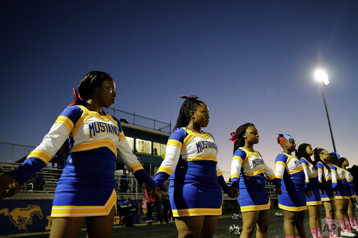 South Robeson High School cheerleaders join hands during the national anthem before a football game in Rowland, N.C., Friday, Oct. 27, 2017. (AP Photo/David Goldman)