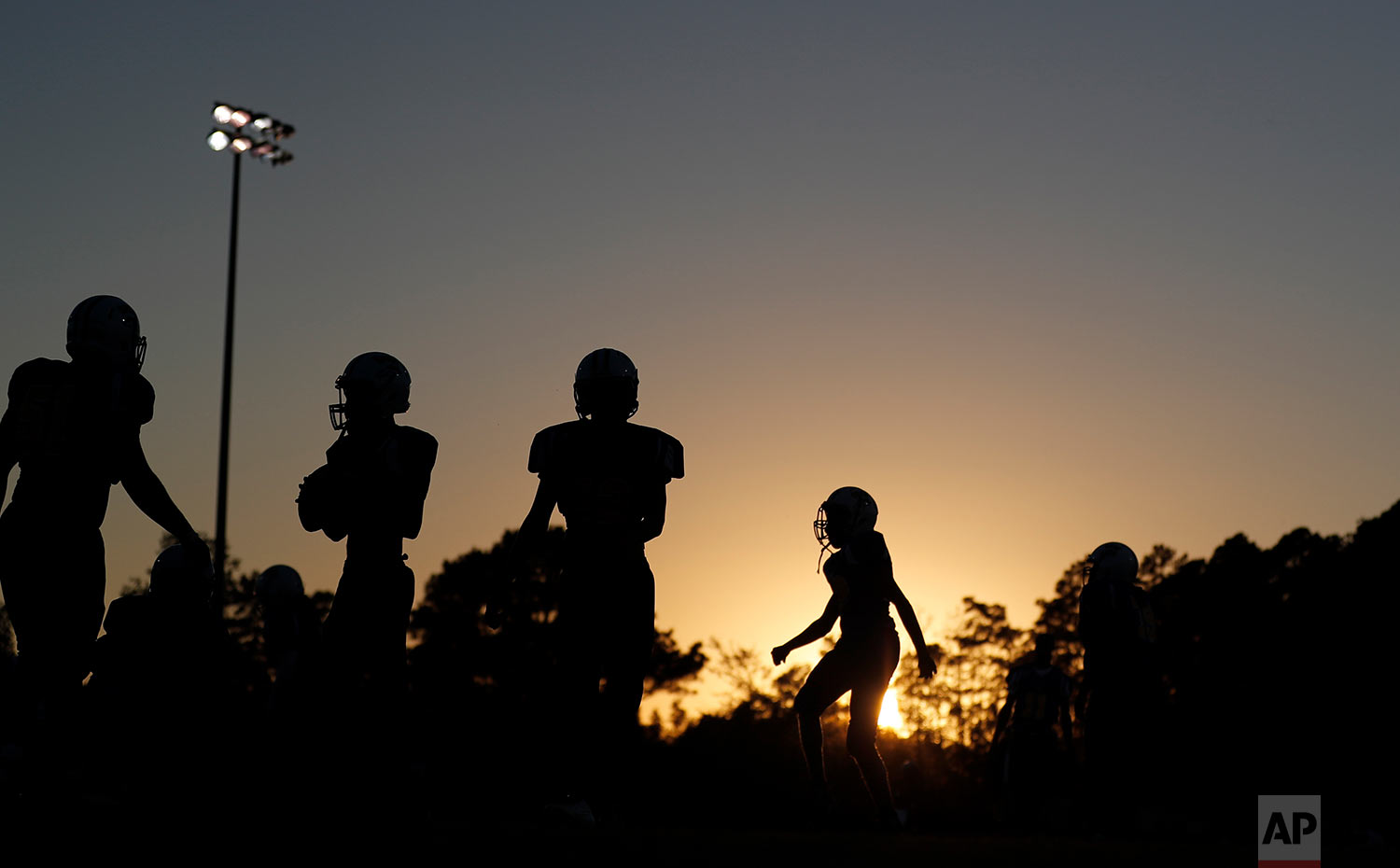 South Robeson High School football players warm up before a game in Rowland, N.C., Friday, Oct. 27, 2017. (AP Photo/David Goldman)