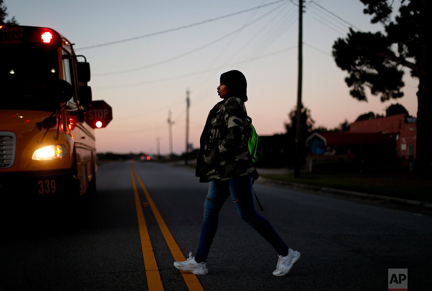 South Robeson High School student and cheerleader Aajah Washington crosses the street to catch the school bus outside her home in Rowland, N.C.(AP Photo/David Goldman)
