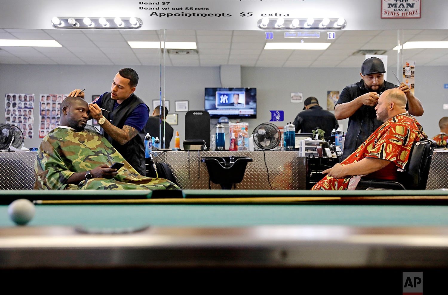Former NFL football player Vonta Leach, left, a Donald Trump critic, gets his hair cut alongside Jamie Locklear, who voted for Trump, at a barbershop in Lumberton, N.C.(AP Photo/David Goldman)