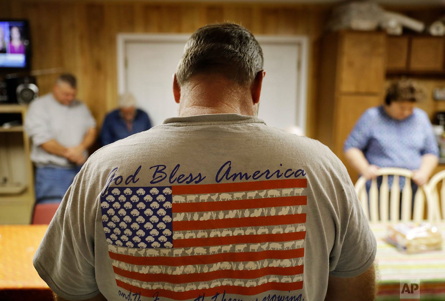 Dinner guests bow their heads in prayer before their weekly gathering at a home in Lumberton, N.C.(AP Photo/David Goldman)