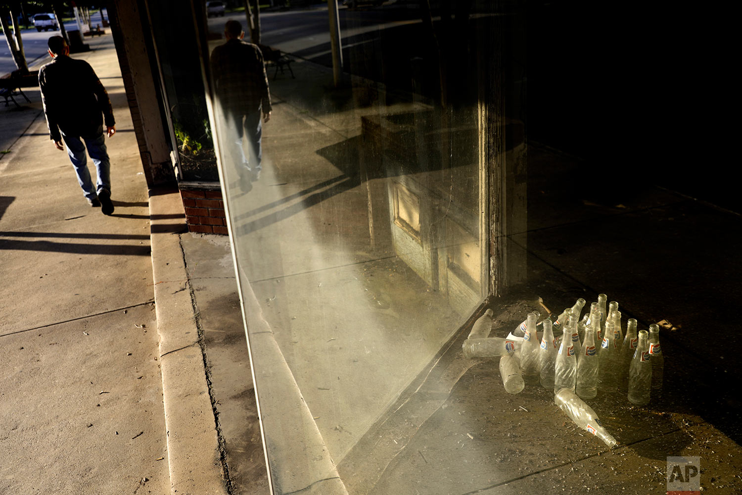 Old soda bottles sit in one of the many vacant storefront windows along West Main Street in Rowland, N.C., Wednesday, Oct. 25, 2017. Rowland, a town in Robeson County, used to make Converse sneakers, T-shirts and pantyhose but the textile economy broke down decades ago and factories moved overseas. (AP Photo/David Goldman)