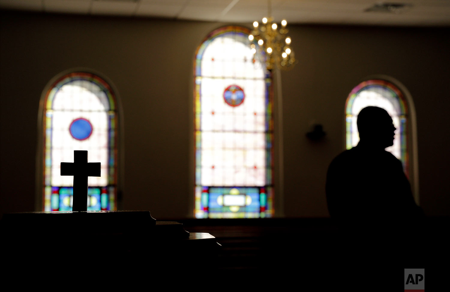 """A cross stands in New Hope United Methodist Church as Rev. Shawn Mitchell, a Navy combat veteran, stands in the sanctuary in Rowland, N.C., Friday, Oct. 27, 2017. """"Southern hospitality lives here in North Carolina. But now we're starting to see it less and less because you are free to be as racist as you want."""" He says President Trump has contributed to that environment. """"Everybody wants their family to be well fed. Everybody wants their family to be well educated. Your children shouldn't be better educated than mine because they're white and mine are black or because you have more money in the bank than I do."""" (AP Photo/David Goldman)"""