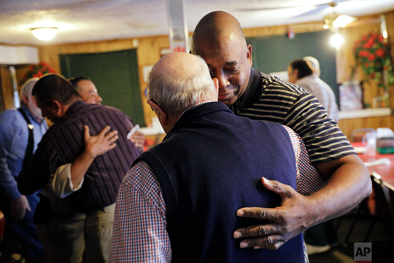 """Walker Davis, right, embraces Bobby Martin at a prayer breakfast at a diner in Lumberton, N.C., Saturday, Oct. 28, 2017. """"We love this isolation because we're comfortable but the lord didn't send Jesus to make us comfortable. Jesus came to change our mindsets,"""" said Davis speaking before the weekly meeting made up of whites, blacks and Native Americans. """"It's a unified body here but we're all from different walks of life and different ministries. This is why I love it here. This is truly a house united, not a house divided."""" (AP Photo/David Goldman)"""