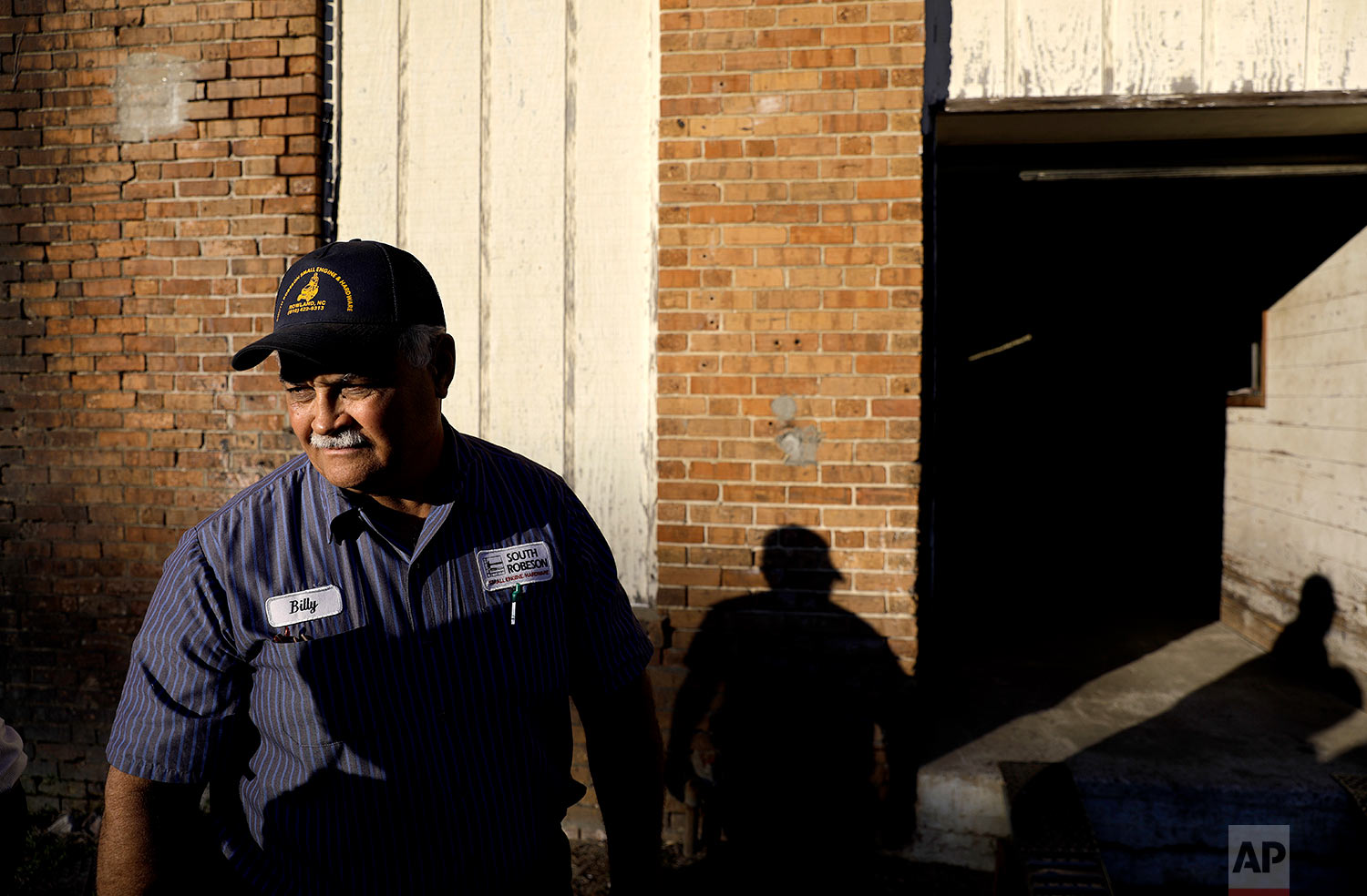"""Billy Hunt, a Native American and a Marine, stands outside his small engine repair shop in Rowland, N.C., Thursday, Oct. 26, 2017. Hunt was hurt, because he thinks the cheerleaders who knelt during the national anthem failed to consider people like him - people who served their country and see the flag as a symbol of that service, of loved ones and limbs lost to war. It seemed to him, like many others here, that they'd chosen a side, without imagining life on the other one. """"I'd like to see it back to people start feeling for each other again,"""" he said, """"instead of - 'it's my idea, it's great, if it's your idea, it sucks.'"""" (AP Photo/David Goldman)"""