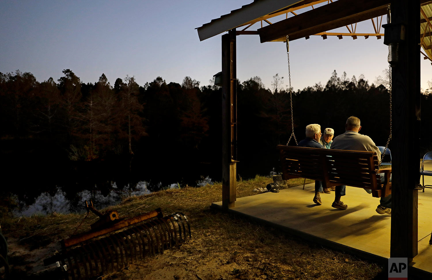 Elton Connor, rear, joins Bruce Kinlaw and Ricky Phillips on the patio before dinner is ready at their weekly gathering at a home in Lumberton, N.C., Thursday, Oct. 26, 2017. Sometimes, the men watch Fox News and talk politics. These days, they turn on football and bemoan the national anthem protests that, to them, represent an unraveling of American values of tradition, patriotism and honor. (AP Photo/David Goldman)