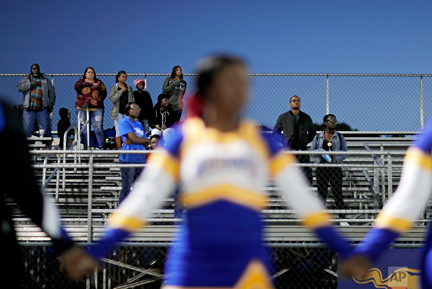 Spectators stand for the national anthem before a South Robeson High School football game in Rowland, N.C., Friday, Oct. 27, 2017. When the cheerleading squad knelt during the national anthem at a recent game, the protest of racial injustice highlighted divisions in Robeson County, North Carolina, the most diverse rural county in America, where voters also helped Donald Trump win the county and the White House. (AP Photo/David Goldman)