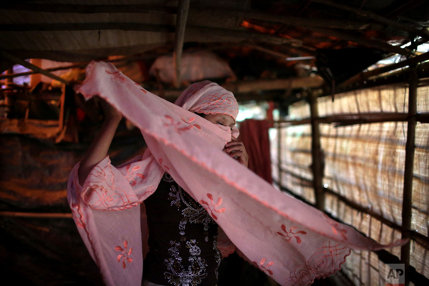 In this Sunday, Nov. 19, 2017, photo, R, 13, who says she was raped by members of Myanmar's armed forces in late August, adjusts her headscarf while photographed in her family's tent in Kutupalong refugee camp in Bangladesh. (AP Photo/Wong Maye-E)