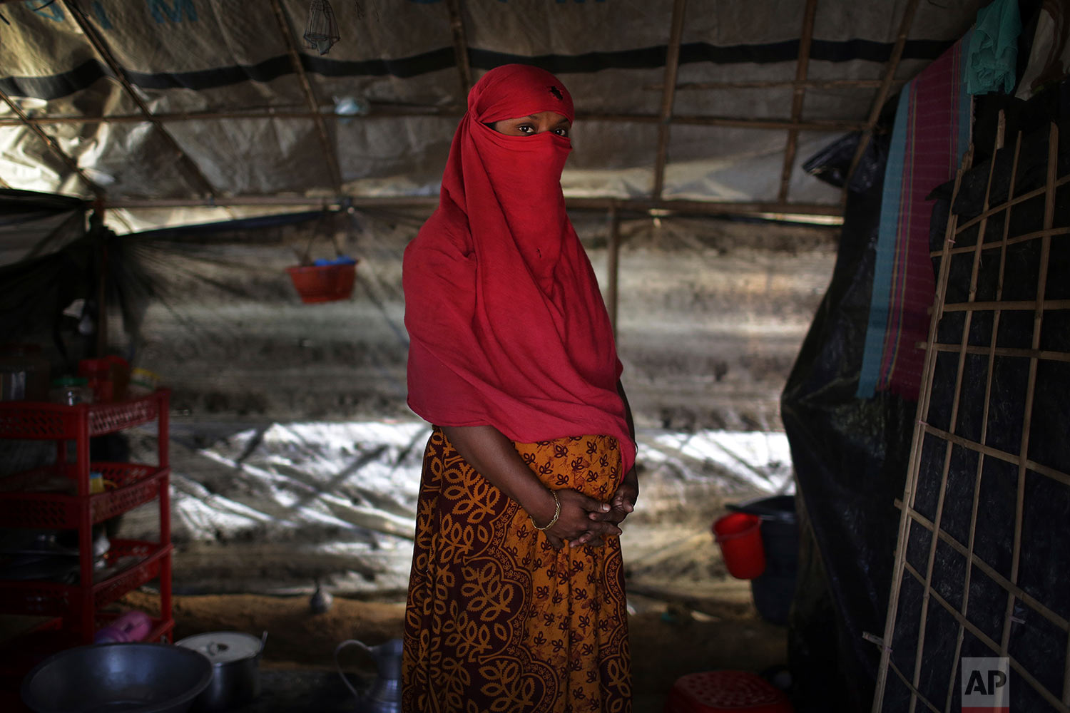 In this Monday, Nov. 20, 2017, photo, F, 22, who says she was raped by members of Myanmar's armed forces in June and again in September, clutches her hands around her pregnant belly as she is photographed in her tent in Kutupalong refugee camp in Bangladesh. (AP Photo/Wong Maye-E)