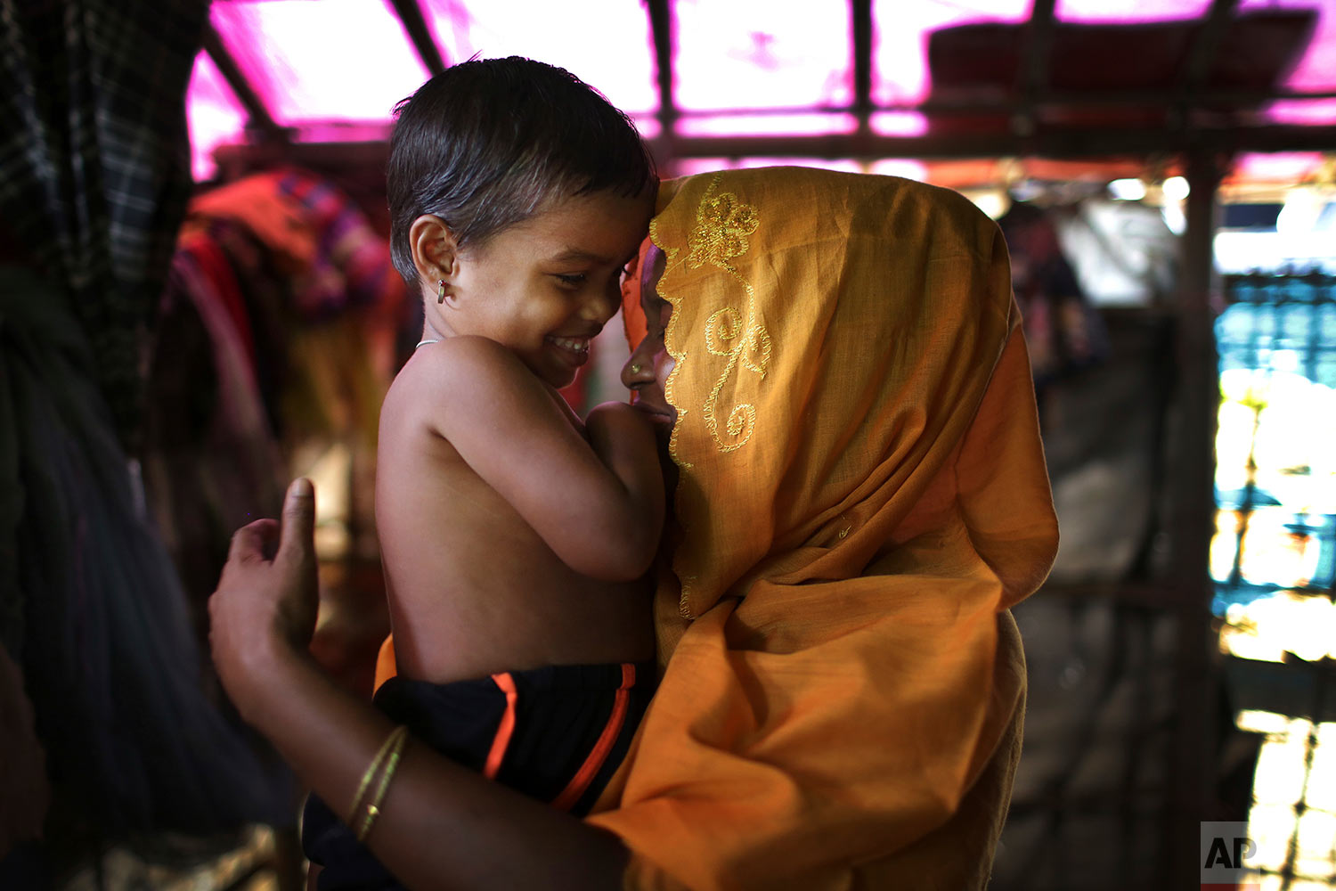 In this Wednesday, Nov. 22, 2017, photo, R, 28, mother of six, who says she was raped by members of Myanmar's armed forces in late August, caresses her daughter while being photographed in her tent in Kutupalong refugee camp in Bangladesh.  (AP Photo/Wong Maye-E)