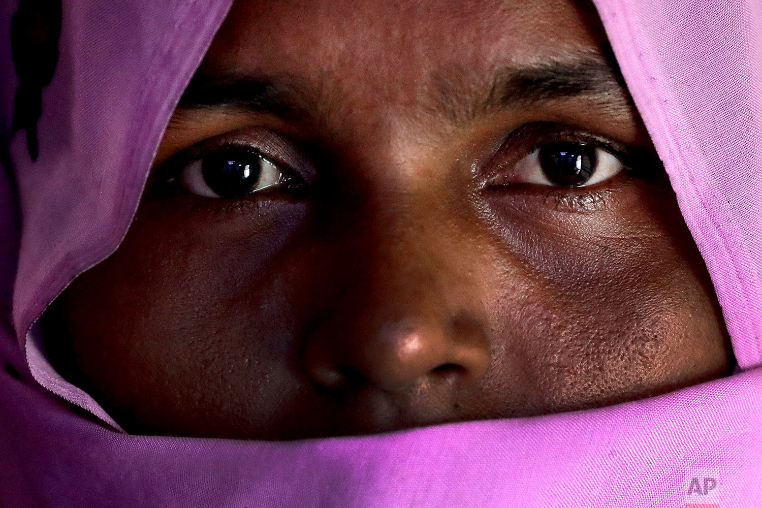 In this Sunday, Nov. 19, 2017, photo, H, 30, mother of six; three children killed, who says she was raped by members of Myanmar's armed forces in late August, is photographed in her friend's tent in Kutupalong refugee camp in Bangladesh.  (AP Photo/Wong Maye-E)