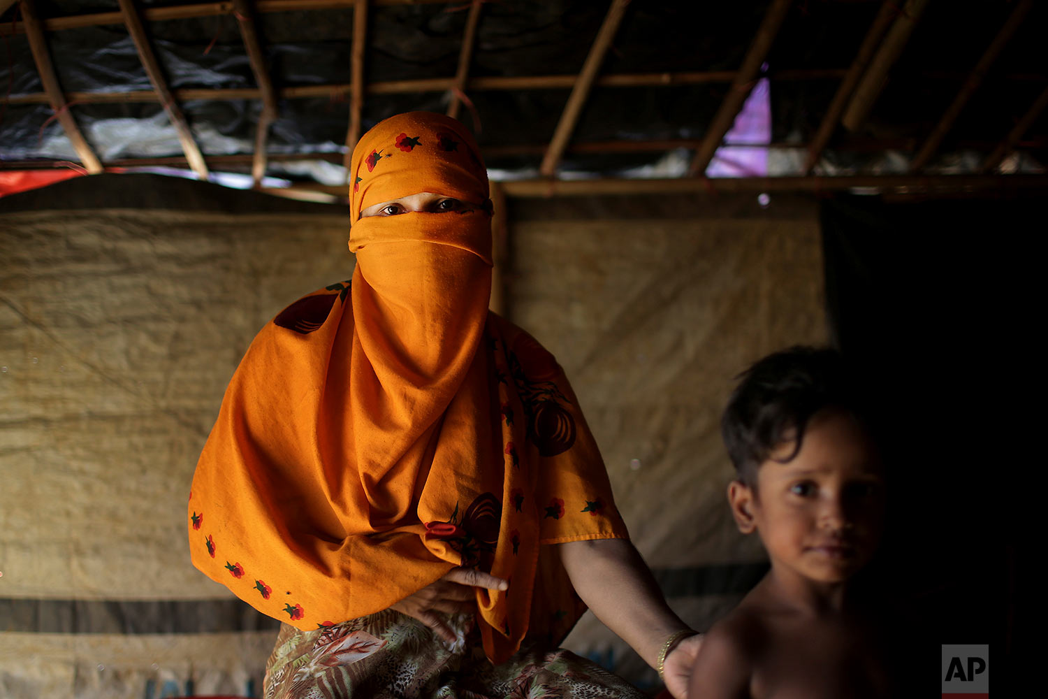 In this Tuesday, Nov. 21, 2017, photo, S, 25, mother of four who's baby girls were killed, and says she was raped by members of Myanmar's armed forces in October, 2016, is photographed with her child next to her in their friend's tent in Kutupalong refugee camp in Bangladesh.  (AP Photo/Wong Maye-E)