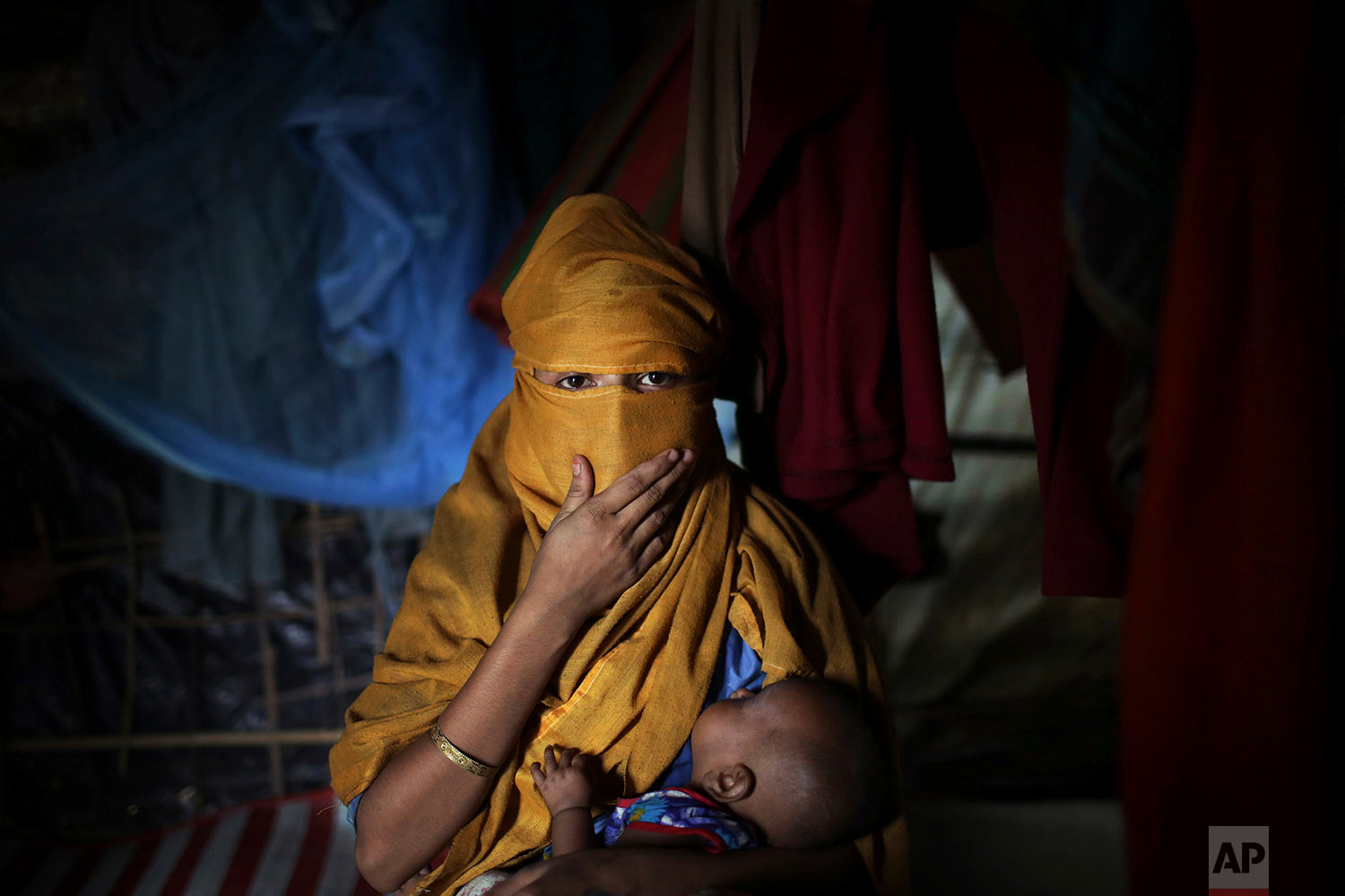 In this Wednesday, Nov. 22, 2017, photo, S, 16, mother of baby boy, who says she was raped by members of Myanmar's armed forces in early August carries her baby while being photographed in her tent in Kutupalong refugee camp in Bangladesh.  (AP Photo/Wong Maye-E)