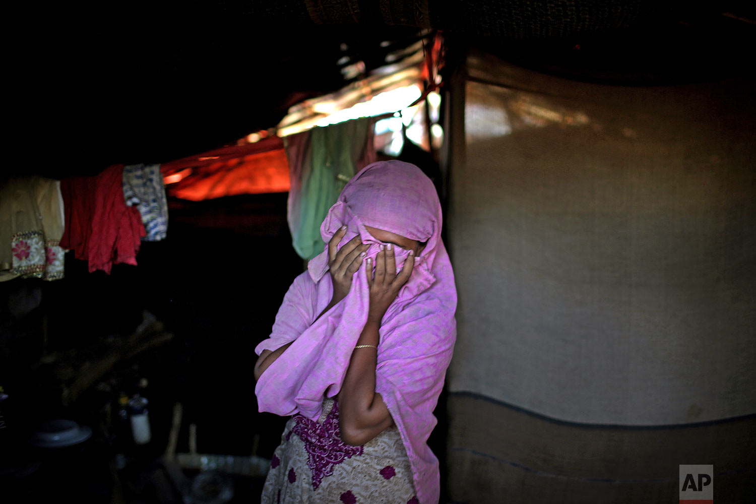 In this Monday, Nov. 20, 2017, photo, A, 20, mother of one, who says she was raped by members of Myanmar's armed forces in late August, covers her face while being photographed in her tent in Kutupalong refugee camp in Bangladesh.  (AP Photo/Wong Maye-E)