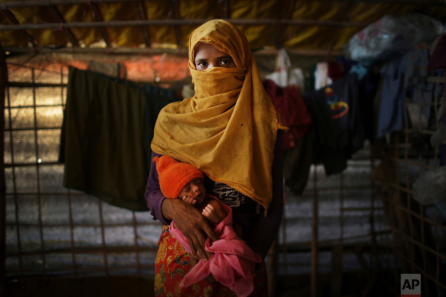 In this Monday, Nov. 20, 2017, photo, K, 30, mother of six who's 3-year-old daughter was killed, who says she was raped by members of Myanmar's armed forces in late August, carries her baby born two months premature, is photographed in her tent in Kutupalong refugee camp in Bangladesh.  (AP Photo/Wong Maye-E)