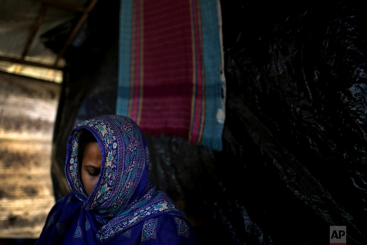 In this Monday, Nov. 20, 2017, photo, M, 35, mother of three, who says she was raped by members of Myanmar's armed forces in late August, is photographed in her friend's tent in Kutupalong refugee camp in Bangladesh.  (AP Photo/Wong Maye-E)