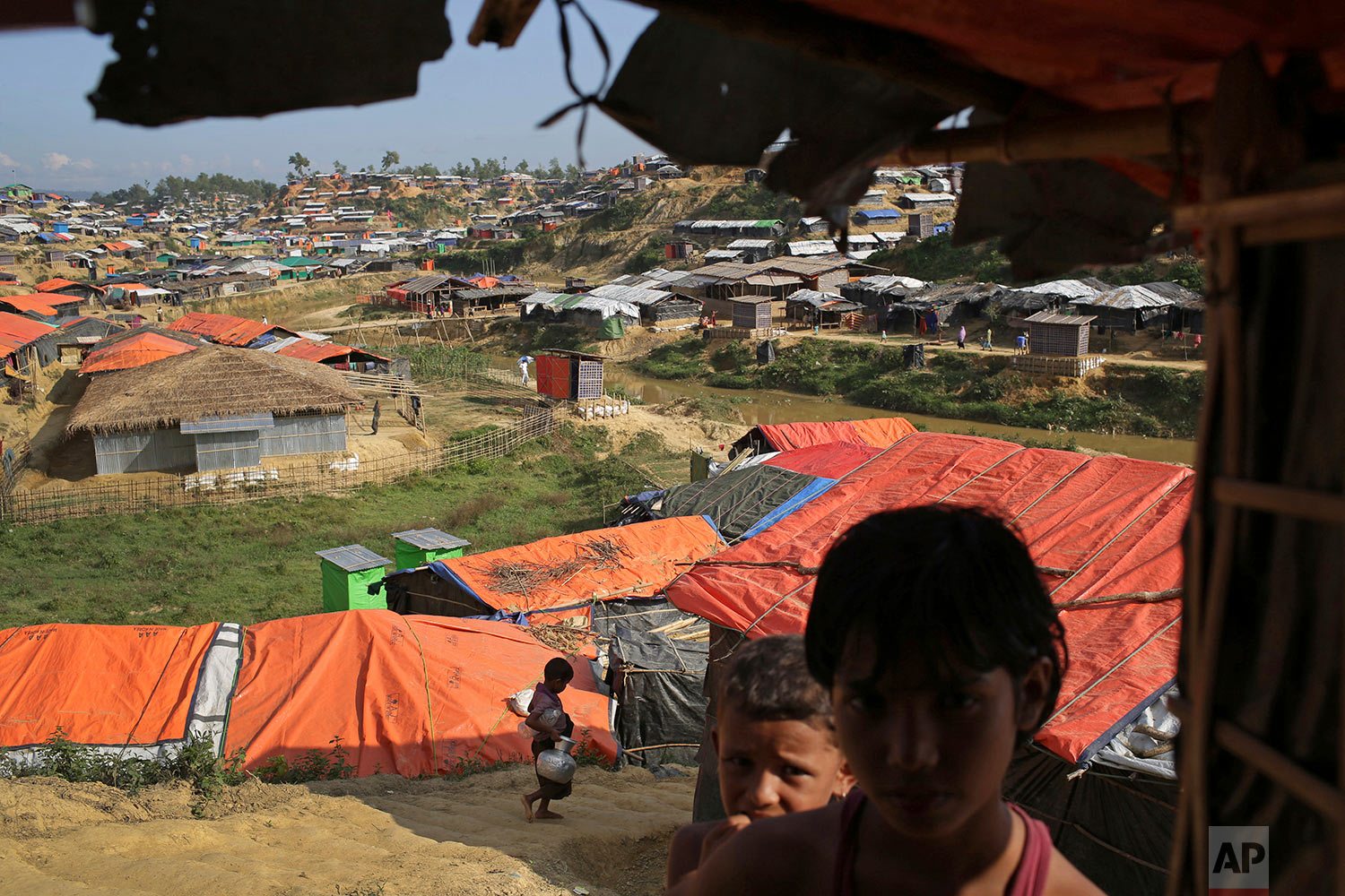In this Sunday, Nov. 19, 2017, photo, Rohingya children stand in the shade of a tent in Kutupalong refugee camp in Bangladesh. (AP Photo/Wong Maye-E)