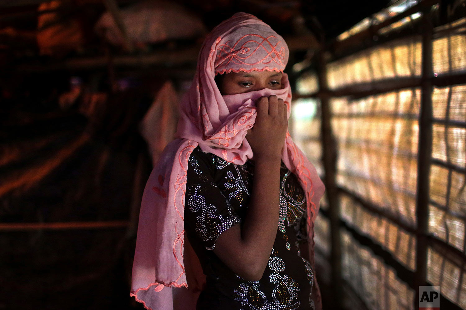 In this Sunday, Nov. 19, 2017, photo, R, 13, covers her face with her headscarf while being photographed in her tent in Kutupalong refugee camp in Bangladesh. (AP Photo/Wong Maye-E)
