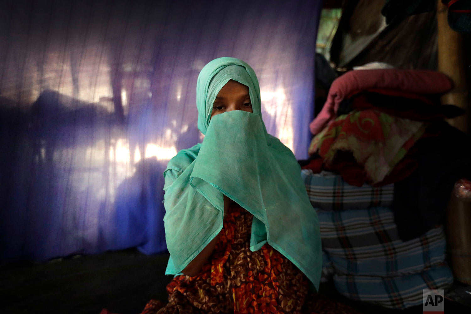 In this Wednesday, Nov. 22, 2017, photo, F, 22, pregnant, prays in her tent in Kutupalong refugee camp in Bangladesh. (AP Photo/Wong Maye-E)