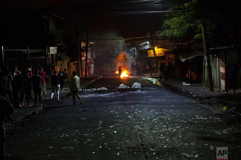 Anti-government protestors gather around barricades in protest during a government imposed dawn-to-dusk curfew in Tegucigalpa, Honduras, Sunday, Dec. 3, 2017. (AP Photo/Rodrigo Abd)