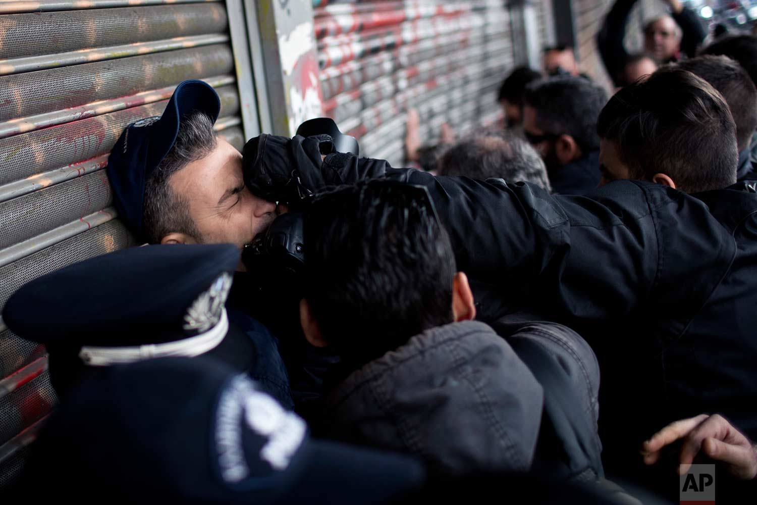 A police officer guarding the main entrance of the Labor ministry is punched by a protester as Communist-backed unionists try to enter the building during a protest in central Athens, Tuesday, Dec. 5, 2017. (AP Photo/Petros Giannakouris)