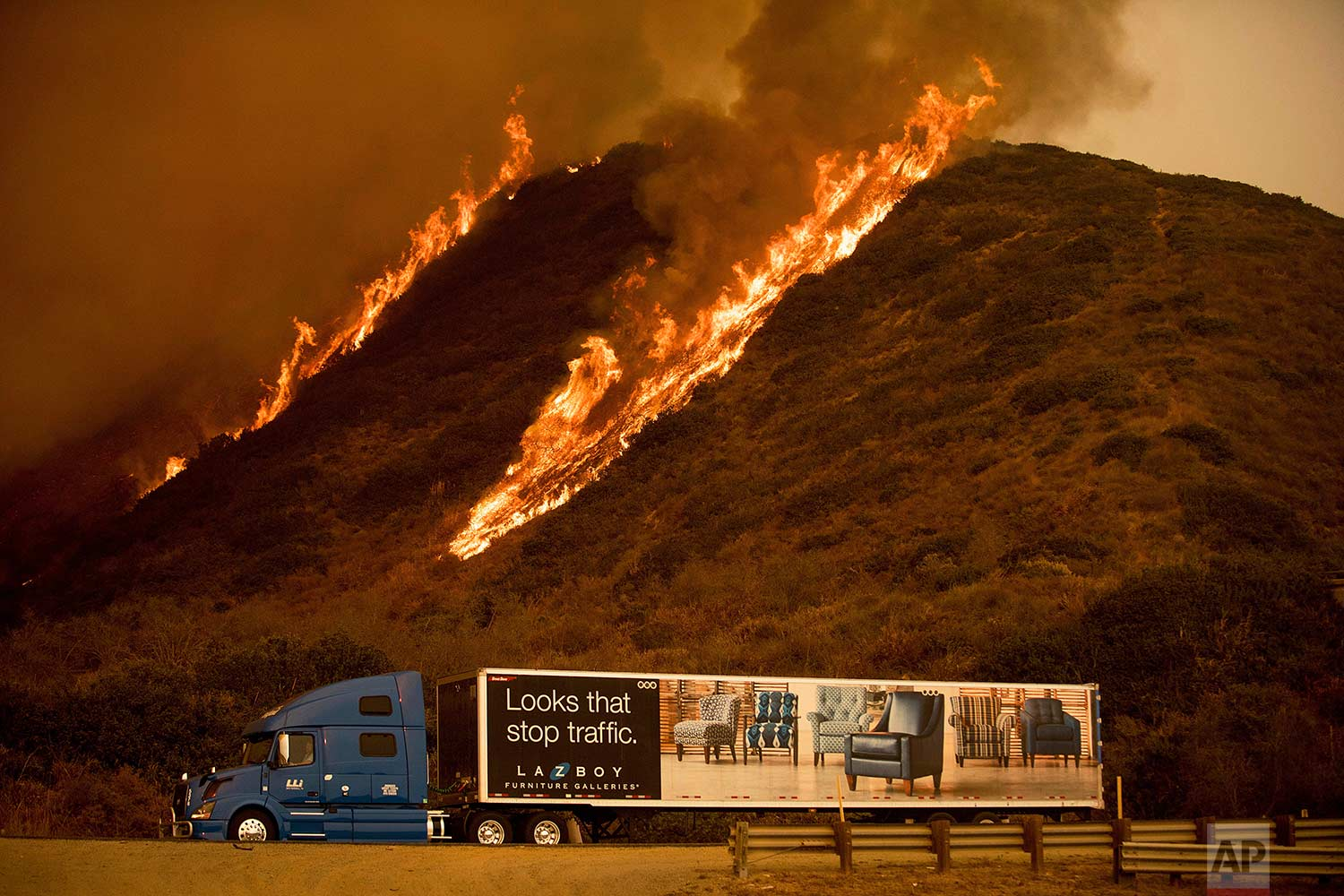 Flames from the Thomas fire burn on a hillside behind a truck on Highway 101 north of Ventura, Calif., on Wednesday, Dec. 6, 2017. (AP Photo/Noah Berger)