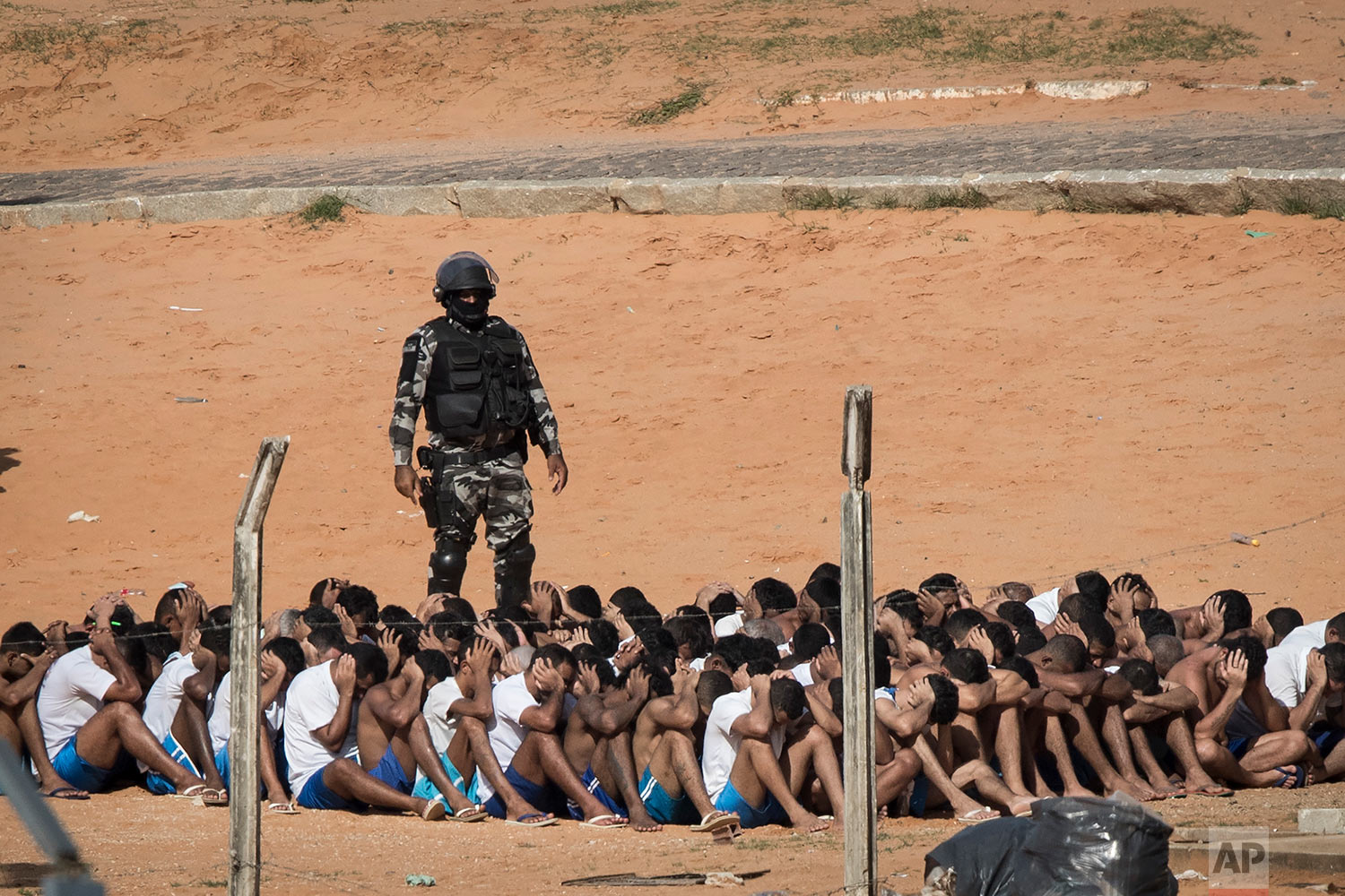 A military police officer conducts a head count of inmates at the Alcacuz prison in Nisia Floresta, Brazil, Tuesday, Jan. 24, 2017. Military police entered the prison in northeastern Brazil where a temporary wall separating two rival gangs was being built, after a week of chaos and fighting between rival gangs that left dozens of inmates dead. (AP Photo/Felipe Dana)