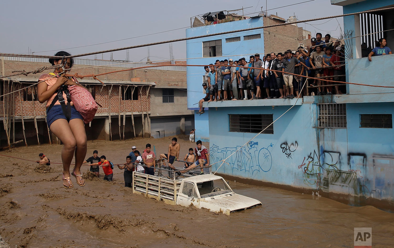 A woman is pulled to safety in a zipline harness in Lima, Peru, Friday, March 17, 2017. Intense rains and mudslides over three days wrought havoc around the Andean nation and caught residents in Lima, a desert city of 10 million where it almost never rains, by surprise. (AP Photo/Martin Mejia)