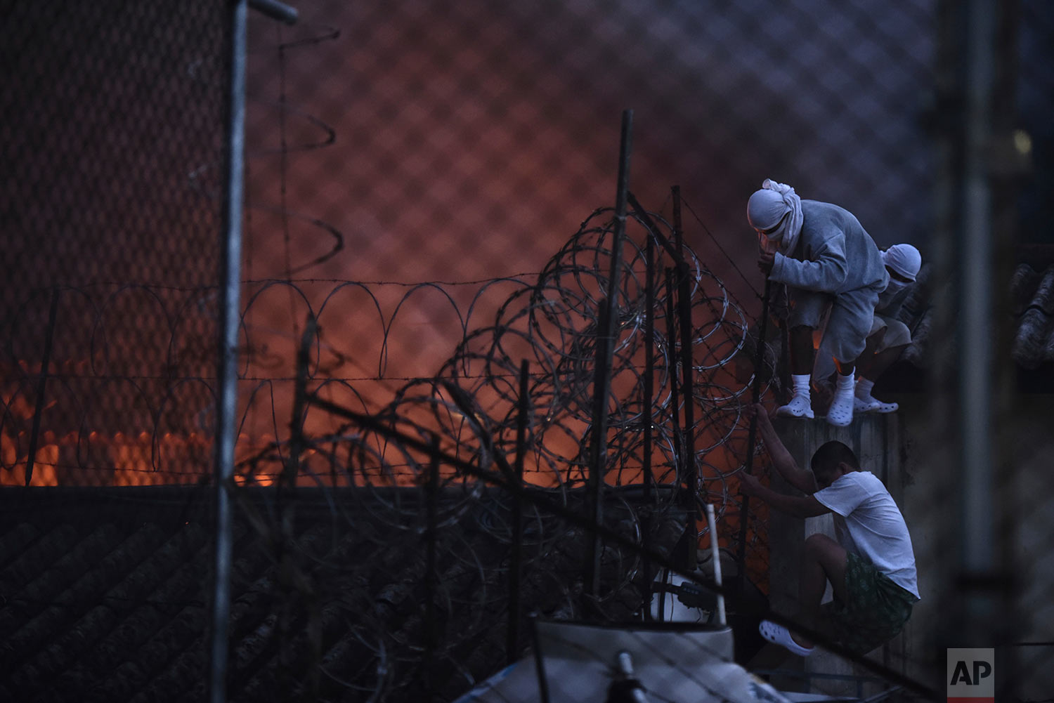 Inmates climb to the roof as a fire breaks out during a riot at the youth and men's reformatory Centro Correccional Etapa II in San Jose Pinula, Guatemala, Sunday, March 19, 2017. At least one man died, a jail monitor, during the riot, according the police spokesman Pablo Castillo. (AP Photo/Oliver de Ros)