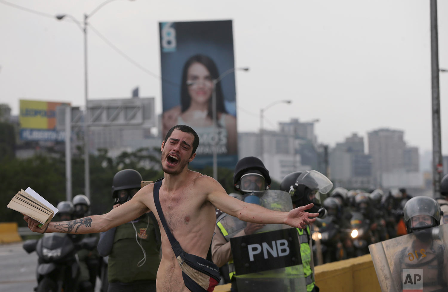 An anti-government protester holds a Bible under the watch of riot police during a march in Caracas, Venezuela, Thursday, April 20, 2017. Tens of thousands of protesters asking for the resignation of President Nicolas Maduro flooded the streets the day after three were killed and hundreds arrested in the biggest anti-government demonstrations in years. (AP Photo/Fernando Llano)