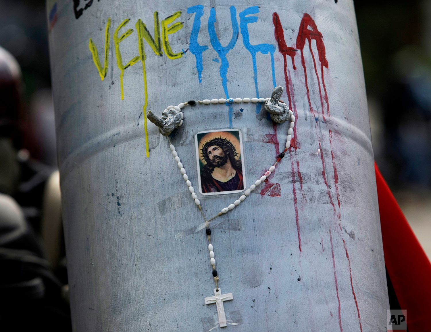 "A protester takes cover from police using this makeshift shield adorned with a rosary, a religious image and Spanish message written above: ""This fight is for you Venezuela"" during a march to the Ombudsman's Office to protest President Nicolas Maduro in Caracas, Venezuela, Monday, May 29, 2017. According to Human Rights Watch, some of the more than 5,000 people detained were beaten, sexually assaulted or given electrical shocks in what the New York-based rights group describes in a report as a level of repression ""unseen in Venezuela in recent memory."" (AP Photo/Fernando Llano)"