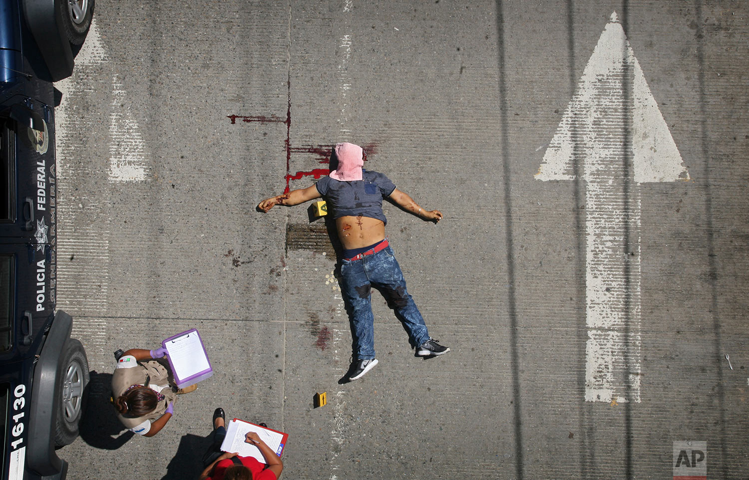 Federal police investigators take notes by the body of a man shot in broad daylight on a central avenue in Acapulco, Mexico, Sunday, Aug. 13, 2017. At least four people were shot in this Pacific coast city Sunday, after Mexico had recently recorded its highest monthly murder total in at least 20 years. (AP Photo/Bernandino Hernandez)