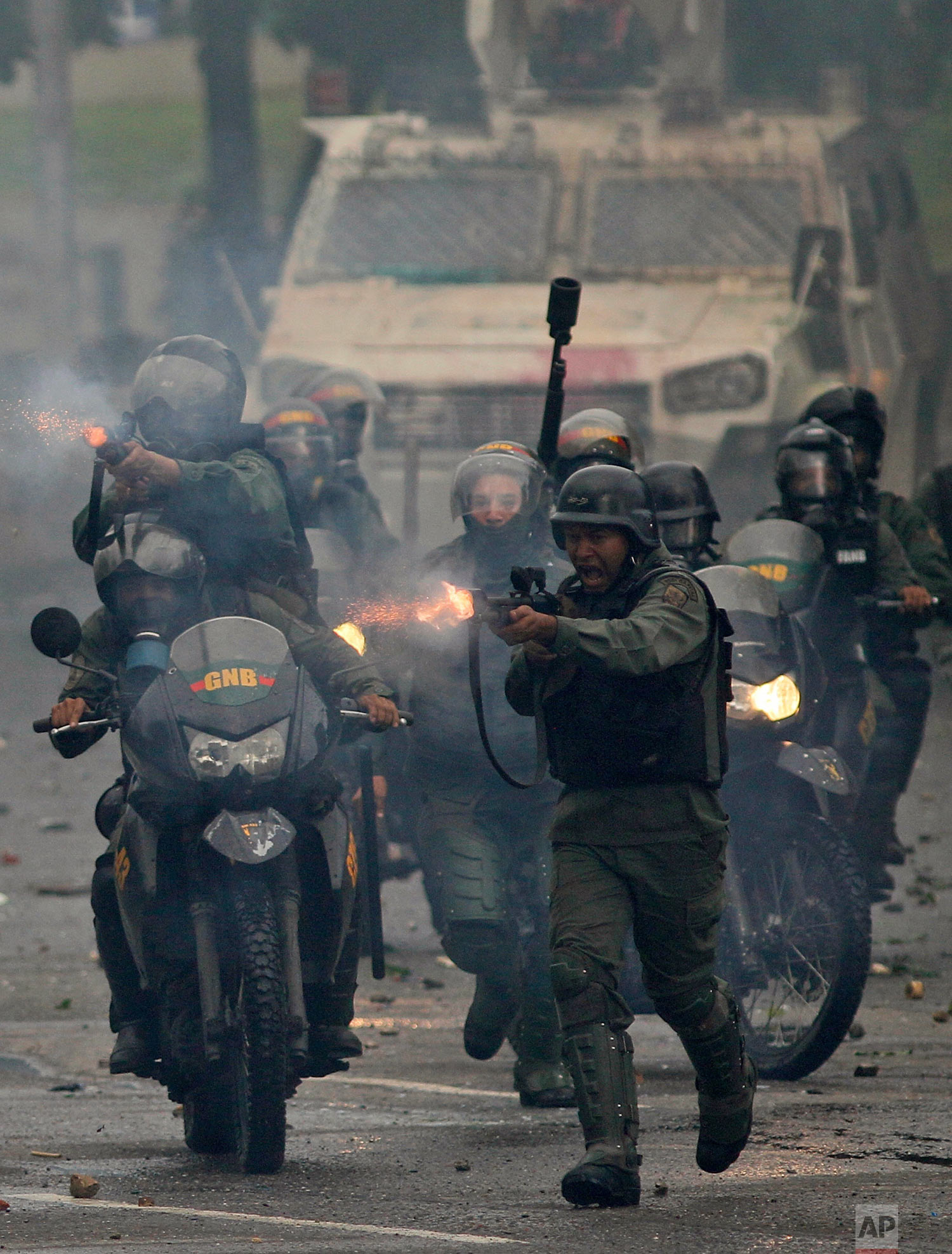 """Bolivarian National Guards fire rubber bullets as they charge anti-government demonstrators in Caracas, Venezuela, Friday, July 28, 2017, two days before the vote to begin the rewriting of Venezuela's constitution. President Nicolas Maduro said the new constitutional assembly's first task in rewriting the constitution would be """"a total transformation"""" of the office of Venezuela's chief prosecutor, a former government loyalist who split from the president. (AP Photo/Ariana Cubillos)"""