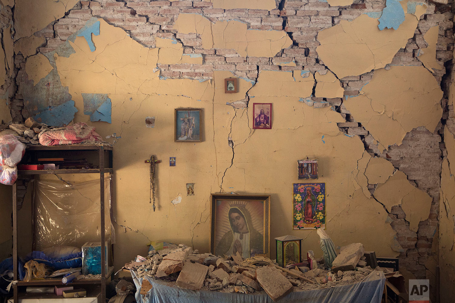 An altar to the Virgin of Guadalupe is covered with fallen debris inside the earth-damaged home where Larissa Garcia, 24, lived with her family in Juchitan, Oaxaca state, Mexico, Saturday, Sept. 9, 2017. The family was caught under rubble when the house partially collapsed, leaving Garcia with a broken arm and her father with a head injury. Her mother, who had to be pulled out from underneath a foot-thick section of wall which collapsed on her back, remained in a wheelchair and unable to walk. (AP Photo/Rebecca Blackwell)