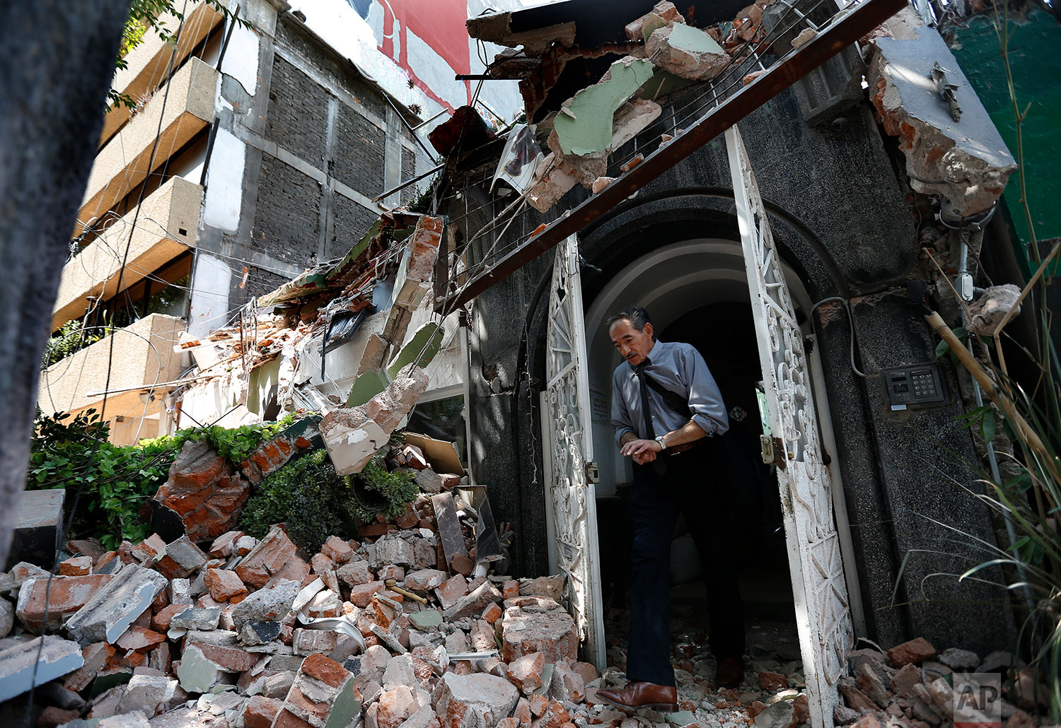 A man walks through a door in a building that collapsed during a 7.1 magnitude earthquake in the Condesa neighborhood of Mexico City, Tuesday, Sept. 19, 2017. (AP Photo/Marco Ugarte)