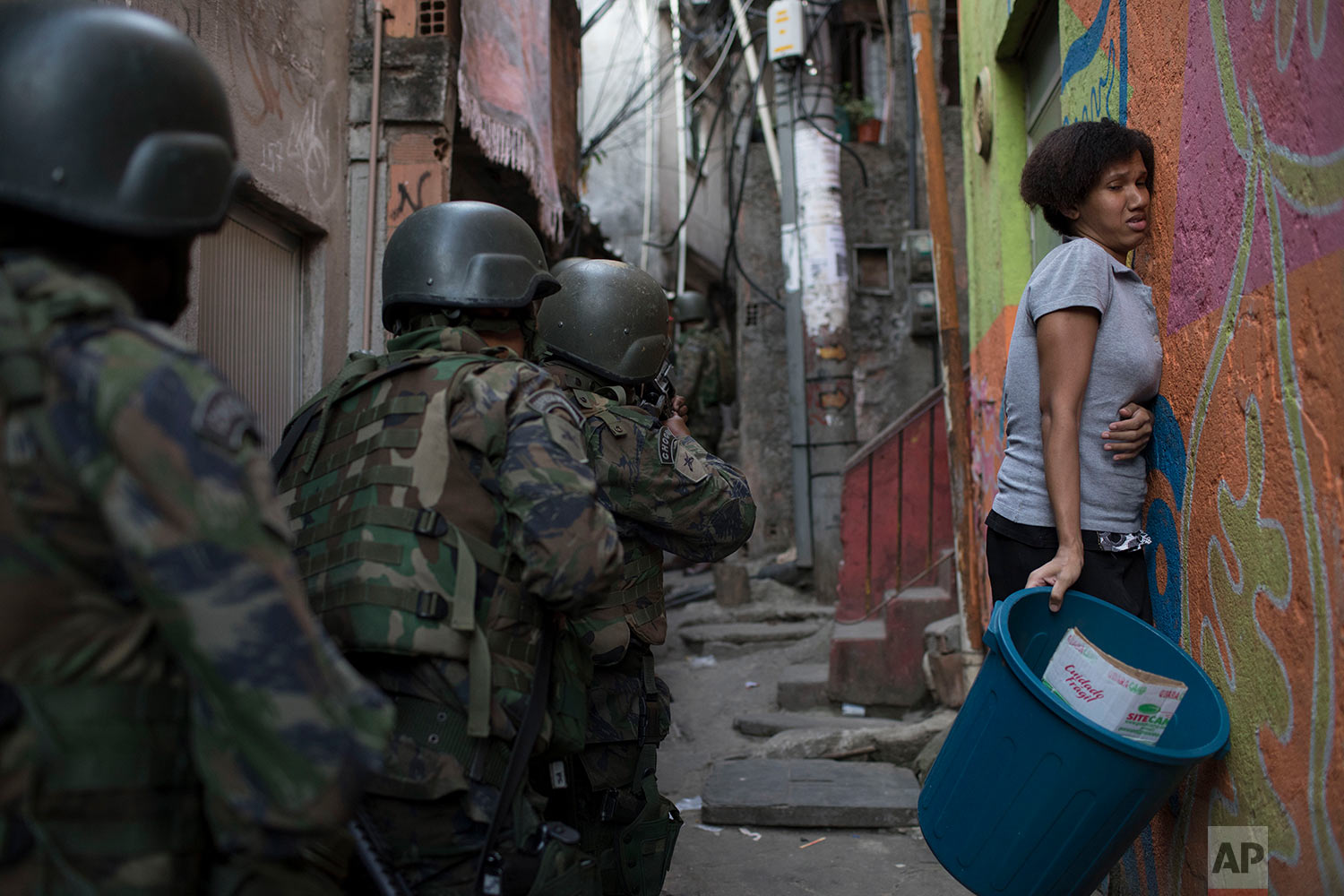 A woman presses herself against the wall as soldiers patrol an alley in Rocinha slum in Rio de Janeiro, Brazil, Friday, Sept. 22, 2017. Shootouts erupted in several areas of Rio de Janeiro on Friday, prompting Brazilian authorities to shut roads, close schools and ask for the army to intervene. (AP Photo/Leo Correa)