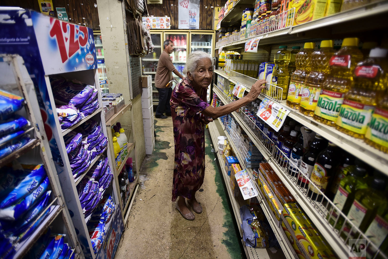 Residents from Juana Matos look for groceries at Catano Mini Market in the middle of a supply shortage caused by the passage of Hurricane Maria in Catano, Puerto Rico, Wednesday, Sept. 27, 2017. Since the devastating impact of the hurricane, the supply of goods has been interrupted in the US territory, causing endless lines in gas stations and comercial centers. (AP Photo/Carlos Giusti)