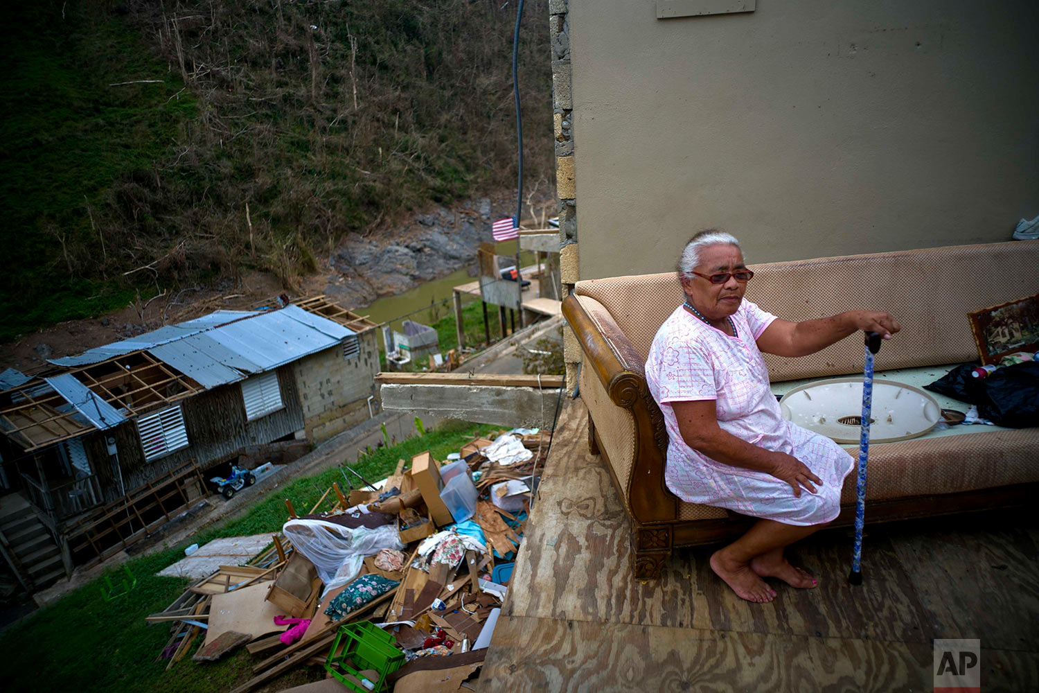 """Juana Sortre Vazquez sits on her soaked couch in what remains of her home, destroyed by Hurricane Maria in the San Lorenza neighborhood of Morovis, Puerto Rico, Saturday, Sept. 30, 2017. """"The night of the hurricane I spent the night at a niece's house. I did not come back for the next nine days because the roads where out. When I made it home I saw that is was all gone. This is a disaster,"""" reflected Vazquez. (AP Photo/Ramon Espinosa)"""
