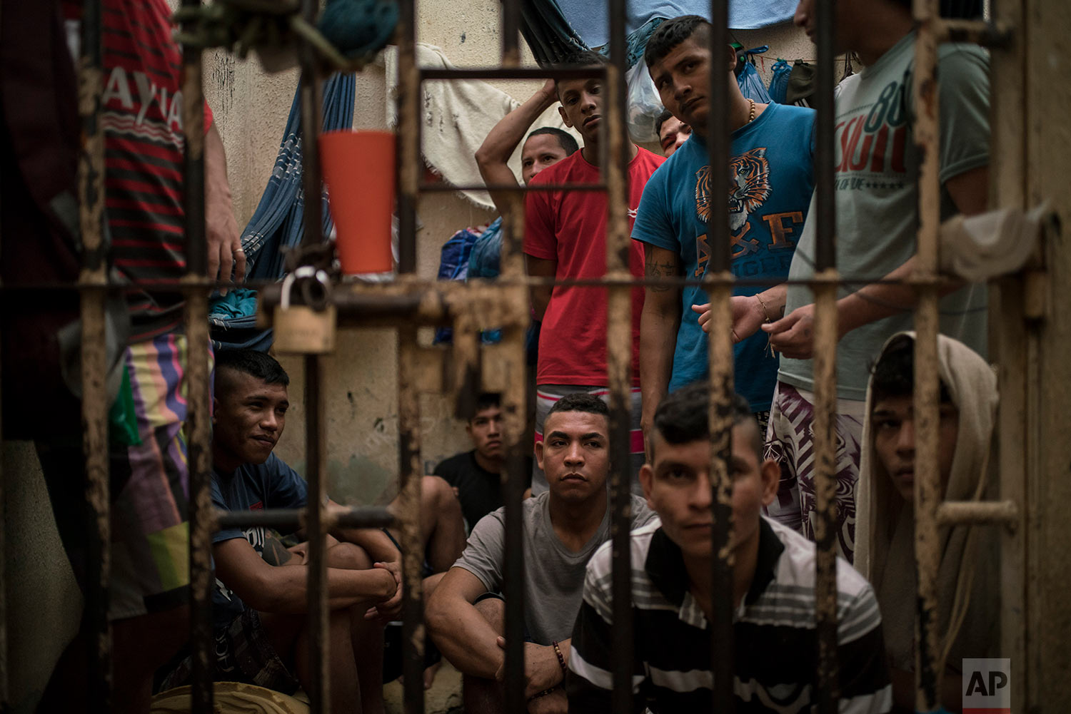 Inmates sit inside an overcrowded cell in a police station near Manaus, Brazil, Monday, Feb. 6, 2017. The beginning of the chain that feeds Brazilian gangs are improvised cells at police stations, where 10 percent of Brazil's more than 600,000 inmates await trial. (AP Photo/Felipe Dana)