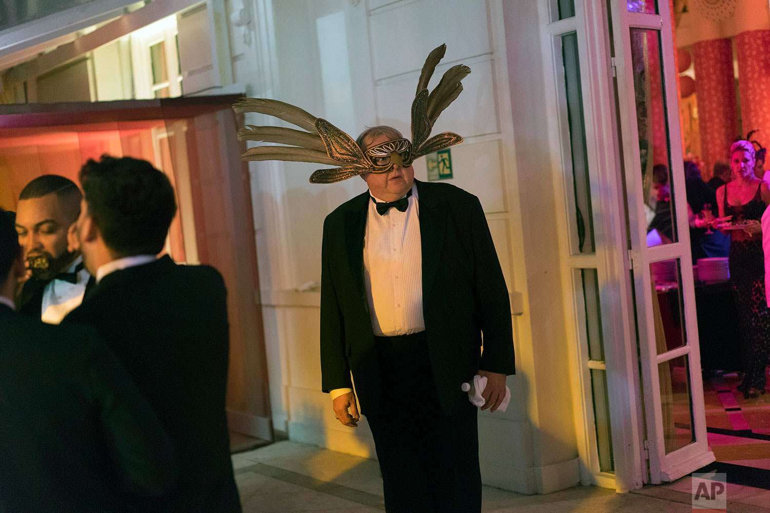 """A guest wearing a mask attends a traditional Carnival ball at the Copacabana Palace hotel in Rio de Janeiro, Brazil, Saturday, Feb. 25, 2017. In stark contrast to the hundreds of hard-charging street parties across Rio that are open to anyone, the """"Baile do Copa"""" bills itself as a fairytale event where the country's elite can see and be seen in a hotel known for both opulence and a lengthy tradition of welcoming world leaders and stars. (AP Photo/Leo Correa)"""