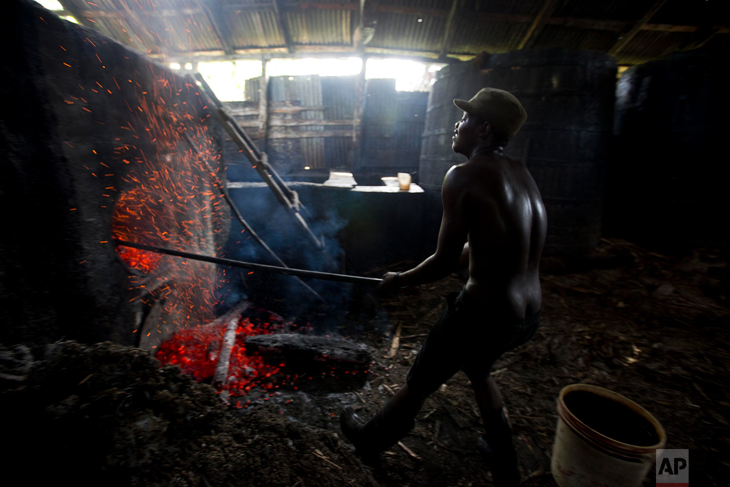 Batel Delciner, 23, removes wood from a furnace to lower the heat that cooks sugar juice at the Ti Jean distillery, which produces clairin, a sugar-based alcoholic drink, in Leogane, Haiti, Friday, June 16, 2017. The broth is cooked for about four hours after a fermentation period of four to eight days. (AP Photo/Dieu Nalio Chery)