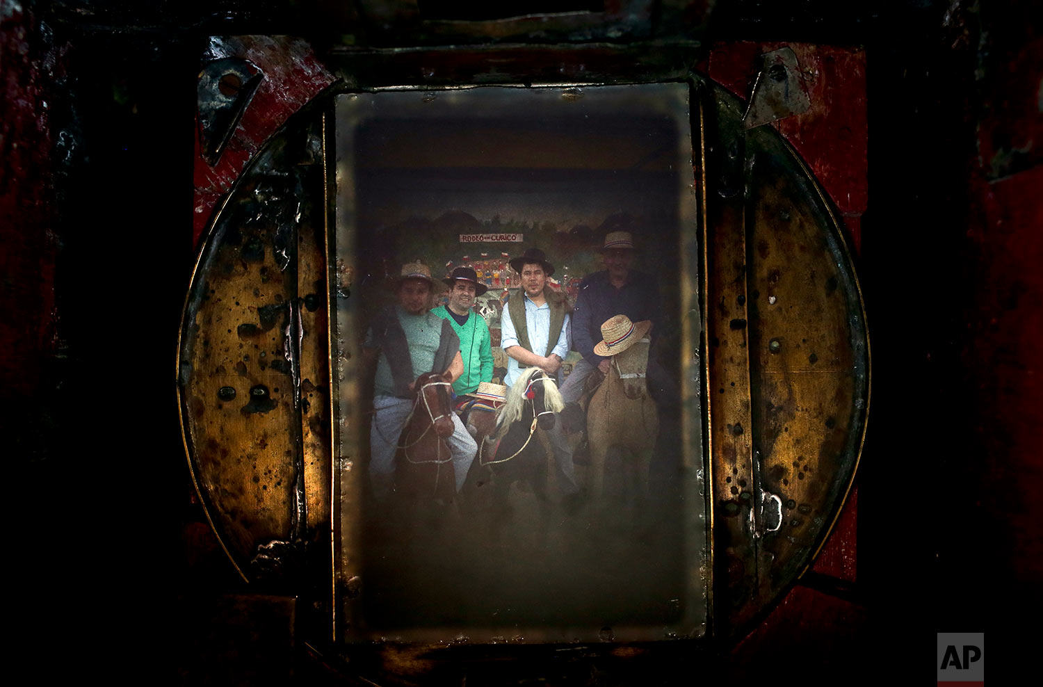 A group of friends fill the viewfinder of Luis Maldonado's old wooden old box camera, during a fair marking Independence Day in Santiago, Chile, Sept. 4, 2016. The image making process lasts about 20 minutes, resulting in a vintage-looking image. (AP Photo/Esteban Felix)