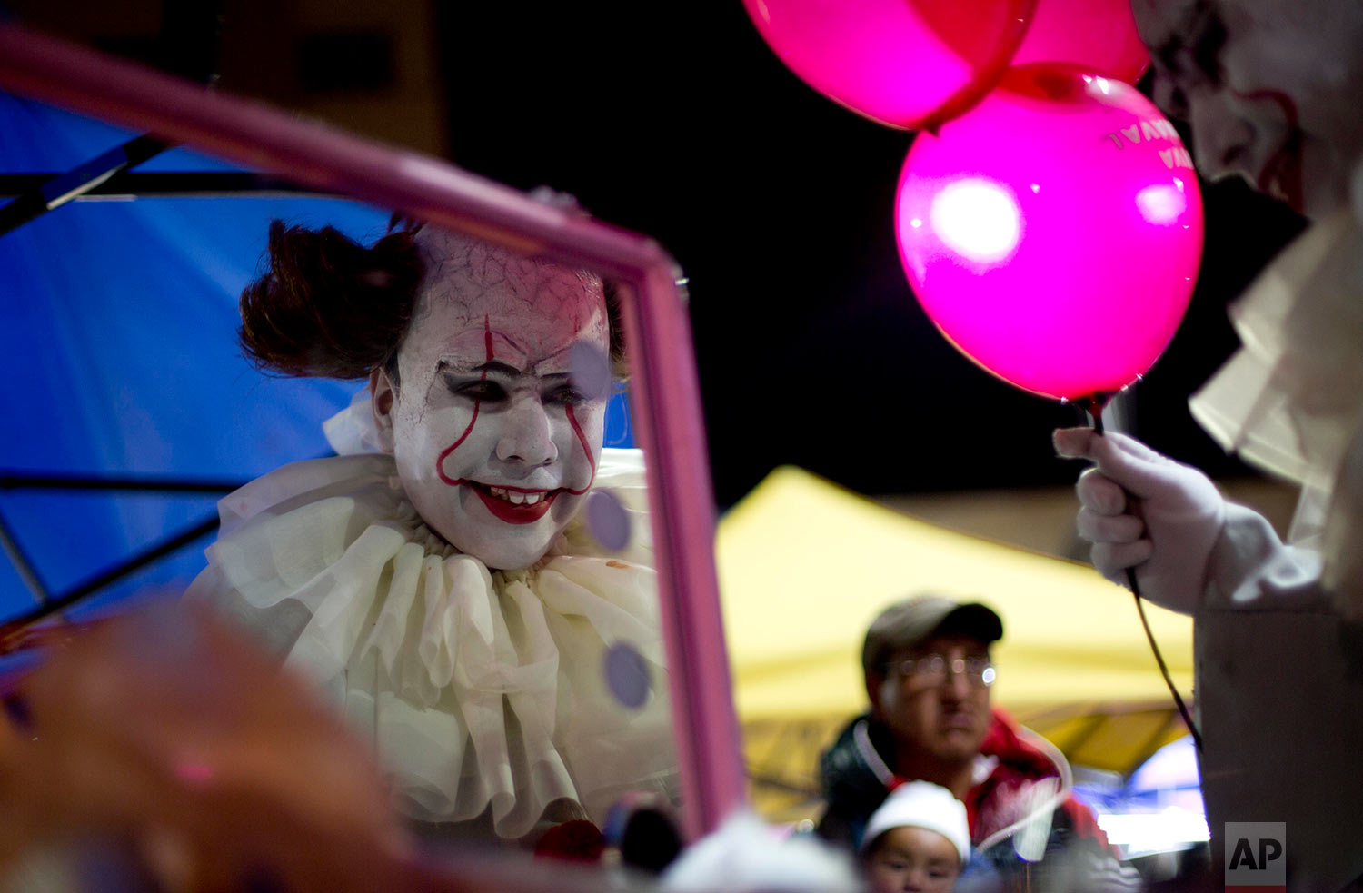 A person dressed in a diabolical clown costume looks in the mirror at the start of the Zombie Walk in La Paz, Bolivia, Saturday, Oct. 28, 2017. The annual walk is a Halloween charity event to collect money to feed street animals, according to organizers. (AP Photo/Juan Karita)