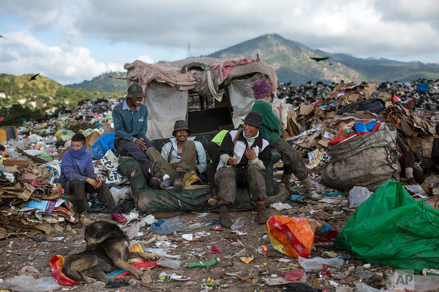 "Men and boys joke around as they take a break from collecting plastic and cardboard to resell, at ""El Crematorio"" or The Crematory, the biggest dump on the outskirts of Tegucigalpa, Honduras, Friday, Nov. 24, 2017. (AP Photo/Rodrigo Abd)"